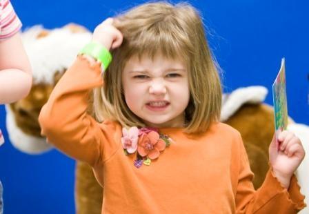 little girl scratching head